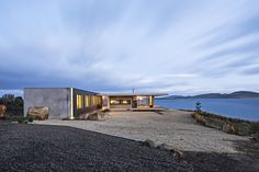 A Semi-Modular Beach House in Tasmania Floats Over a Site That Survived a Bushfire - Photo 2 of 9 - The Younger family vacation home is a semi-modular structure made of wood, steel, glass, and precast concrete. It's surrounded by Tasman gold gravel, which acts as a buffer zone in case of a bushfire. A building-height LED light accentuates an exterior corner. Styled by Julia Landgren