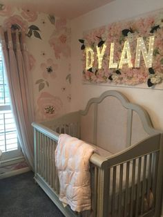 Pretty floral baby girl nursery. We adore how they framed the marquee lights to make a gorgeous nursery name wall sign!