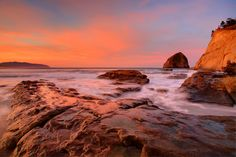 Sunrise photo of Haystack Rock from the tide pools at Cape Kiwanda in Pacific City, Oregon.