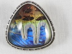Antique British silver triangular shaped morpho butterfly wing brooch. Circa 1920s Hallmarked  Silver . 1 h x 1 w ( at widest ) . 6.4 gms Amazing condition. Enlarge the close up, the colours and texture that only nature can create.  Morpho butterfly wing jewellery became popular in Britain in the 20s and 30s. In 1924, at the British Empire Exhibition, Thomas L.Mott introduced this precious jewellery. Finely made of sterling silver and the South American morpho butterfly wing.  Rare and…