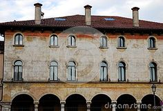 Photo taken in an historic and important building in Vicenza in Veneto (Italy). In the picture you can see almost the entire facade of the historic building which is situated near the river Bacchiglione. Downstairs arches and its columns surround the large porch. In the two upper floors you are seen six arched windows without shutters on each floor. Over the roof of the three fireplaces in the shape of cylinder interrupt the blue sky.