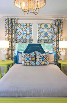 source: Lucy and Company  Modern green & blue boy's bedroom with Stray Dog Designs Courtney Pendant, bed in front of window, peacock blue velvet headboard with silver nailhead trim, neon green round tables nightstands, white penguin lamps, green bench and blue, gray & yellow geometric pattern pillows, roman shades and curtains.