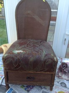 A dark and dreary Lloyd loom chair with a draw underneath
