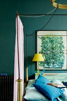 Decorating with dark paint doesn't mean you'll end up with a room of Stygian gloom. In fact the very opposite. Used properly drama and atmosphere await. Like this bedroom, where dark blue paint and citrus accessories.