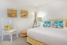 This lively bedroom features a yellow and white geometric print upholstered bed with colorful floral throw pillows. A white wooden armchair is positioned next to a natural wicker ottoman, providing a perfect spot for relaxing, while decorative skis and a matching set of modern paintings add a finishing touch.
