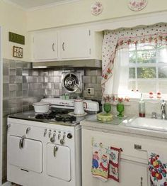 <3 This 1950s Chambers cookstove helped seal the deal when Krissy and her husband were househunting. The kitchen still has its original cabinetry. Krissy added red accents, like   the antique red-and-white enamelware and the 1940s teapot curtains.