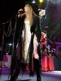 A more recent stage shot of Stevie Nicks featuring here signature platform boots, top hat and long flowing gowns.