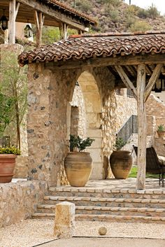 stone covered porch with ceramic pots is perfect French Country style  (by Don Ziebell)