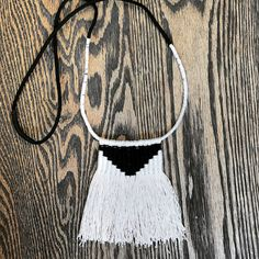 This piece is a true wearable art piece. Hand knotted and woven by me. Thick black cotton rope wrapped/ knotted with a taupe cotton string. The fringe hangs in the middle with woven black and white thread. Its like a mini wall hanging  Length is 35inches  Piece is not adjustable but it your looking for a shorter size please let me know.  Each piece is individually handmade and may vary slightly from the images shown