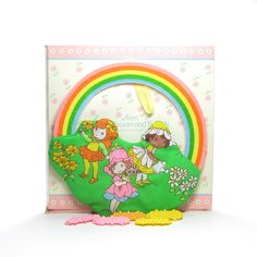 This vintage Little Blossom wall hanging is a barrette holder and comes with 5 plastic flower-shaped barrettes. The barrette holder is made of cloth and features Little Blossom with her friends Scampe