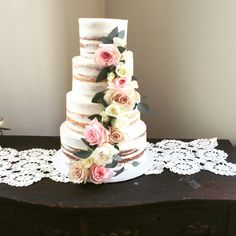 Gorgeous semi naked wedding cake accented with cascading roses and greenery!