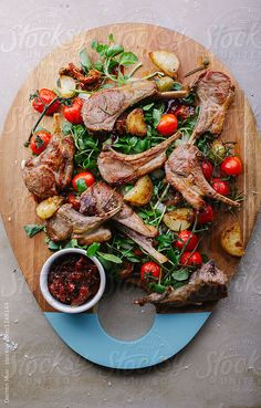 Lamb salad. Roasted lamb chop salad with potato and roasted vine tomatoes. by Darren Muir for Stocksy United