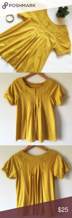"{Anthropologie} Pleated Swing Blouse Deletta for Anthropologie cotton blouse. Flowy and relaxed with pleated detail on front and back. Braided, embroidered collar with three flower buttons. Color: Mustard yellow. 18"" pit to pit. 24"" shoulder to bottom of hem. 100% cotton. Good preloved condition. Anthropologie Tops Blouses"