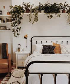 A Perfect  Bedroom for  Relaxing | White walls, neutral colours, open shelving, plants, a plush rug,  patterned throw pillows, black iron bed frame, and a leather reading chair