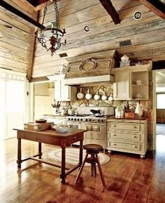An open kitchen with a lofted ceiling features custom cabinetry and a cool, rustic vibe. - Traditional Home ® / Photo: Colleen Duffley / Design: Randy Korand and Dan Belman