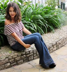 off shoulder striped blouse with flared jeans. Long bob hair.