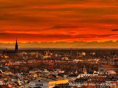 Sunset over de city of Munich wif de Alps Mountains in de background in Germany