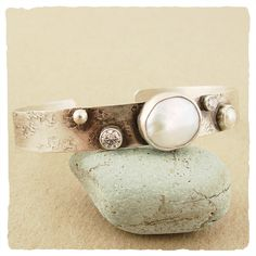 "Unique pearls are hand picked and bezel set into the luxurious cuff, offset with a 4mm white cz to create a truly individual piece.  Oxidized sterling silver with white freshwater pearls and white cz.  Cuff is 3/8"" wide"