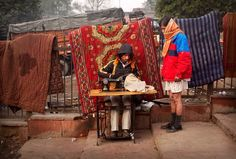 India. One of things I will never forget: directly outside the gates of upper middle class homes (where I was lucky enough to be a guest) would be the very poor plying their trade. This gentleman is sewing; the one I saw was ironing (using a flatiron heated with coals.)
