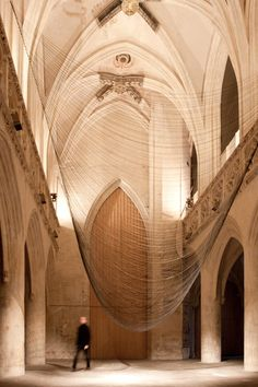 French artist David Letellier has created a  kinetic sound sculpture for Saint Sauveur Chapel of Caen, France entitled 'Caten'. Letellier developed the work from 300 fine wires suspended from two ropes and given shape by gravity and the slow shifting of rotating arms connected to the four corners of the stringed fabric. The name is derived from the term catenary, which describes the plane curve formed by a rope hanging between two points.