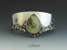 Silver Cuff, Bracelet, Prehnite Cuff, Handmade Bracelet, Metalsmith Jewelry, Sterling Silver, Prehnite, LjBjewelry  A great statement cuff bracelet made of sterling silver and a lovely prehnite cabochon set in a bezel. Small silver granules were randomly soldered along the edge of the cuff to create a unique texture.  The cuff has been oxidized.  The cuff is approximately 5.25 inches in length and the opening is 1.25 inches.   The cuff fits a wrist with a 6.5 inch circumference.  Shipping…
