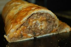 Pastry Stuffed Meatloaf | Roll 2 pounds lean ground beef 1 cup dry bread crumbs 2 eggs beaten 1 chopped onion 1 chopped bell pepper 1 cup chopped mushrooms 1 cup chopped black olives 3/4 teaspoon salt 1 teaspoon leaf oregano 1 15 oz can tomato sauce  1 cup shredded mozzarella cheese 1 cup shredded cheddar cheese 2 cans crescent rolls