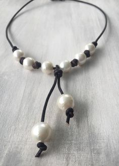This leather and pearl necklace is absolutely gorgeous. The necklace is made with high luster 13 mm freshwater pearls on a 2 mm dark brown leather cord. This is a timeless piece and for you to enjoy for many years to come. For the clasp I also used a 9.5 mm freshwater pearl. Checkout my other leather pearl jewelry for matching bracelets and earrings.  Length of necklace shown: 18 inches  Want a different length please choose from the scroll down menu. Also available in black and light brown…