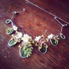 Floral necklace of orchids, salal leaves, seeded eucalyptus and silver wire. Designed by Angela Darrah AIFD.