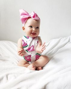 cute baby in a watermelon outfit and big pink bow sitting on white bed