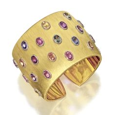 18 KARAT GOLD AND MULTI-COLORED SAPPHIRE BANGLE-BRACELET, BUCCELLATI The hinged cuff of satin-finished gold, studded with 23 oval sapphires of lavender, pink, blue, green, orange and yellow color, each within a white gold textured bezel, signed M. Buccellati.  With signed box.
