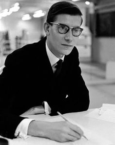 Yves Henri Donat Matthieu Saint Laurent (1936-2008) was best known as an influential European fashion designer who impacted fashion in the 1960s to the present day. In 1966, he launched his own fashion labels, where his adaptations of tuxedos for women, the sheer blouse & jumpsuit garnered him fame. He also outfitted women in blazers & smoking jackets, & introduced the pea coat to the runway.
