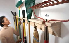 Create a simple long-handled tool hanger out of two 1x4s. On the first one, drill a series of 2-in. holes along the edge of the board. The trick is to center each hole about 1 in. from the edge. That leaves a 1-1/2-in. slot in the front that you can slip the handles through. Space the holes to accommodate whatever it is you're hanging. Screw that board to another 1x4 for the back and add 45-degree brackets to keep it from sagging. If you wish, pound nails into the vertical board to hang…