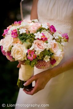 Bridal bouquet composed of cream roses, pink freesia, berzillia berries, pink roses, mini pink dahlias and stephanotis
