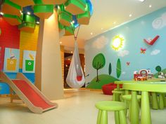 This bright and colorful playroom brings the outdoors in with a handpainted mural, kid-size tables, indoor swing, a slide and column made to look like a tree.