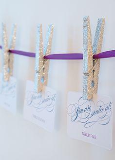 Guirnalda hecha con pinzas con purpurina color plata para indicar los asientos de cada invitado