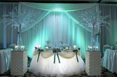 SOFT AQUA/MINT LIGHTS LIKE THE OCEAN... LOVE IT!!!!!    COULD DO THE PALM TREE FEATHERS ON STANDS... THIS LIGHTING WITH KARENS TABLE SETTINGS!!!  YES!!!!
