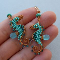 Earrings | Pippi Konstanski.   Wire wrapped seahorses are made with copper wire and turquoise colored glass seed beads. The dorsal fins are two briolettes of blue quartz, and the eyes and leverback earwires are 14K gold filled.
