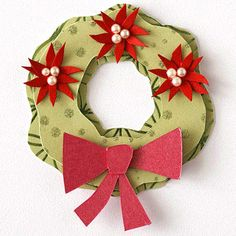 Design by Vicki Boutin and Jennifer Perks Flocked and foiled green papers give texture to a holiday wreath paper piecing. Layer the wreath shapes with adhesive foam to add dimension, and top two star shapes with mini pearls to create festive poinsettias.  SOURCES: Cardstock: Prism Papers (pink metallic), Stampin' Up! (red). Patterned paper: Chatterbox. Pearls: KaiserCraft.