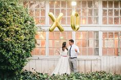 Love these X O balloons held by the bride and groom!  Cute photo prop idea.  Photo: Megan Welker. Balloons: Oh! Shiny Paper Co. | http://emmalinebride.com/decor/giant-letter-balloons-weddings/