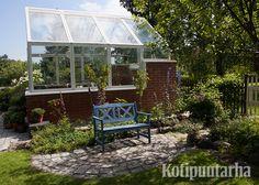 Korkea kasvihuone antaa sopivasti tuulensuojaa tälle istuskelupenkille, josta aukeaa kaunis näkymä koristepuutarhaan.