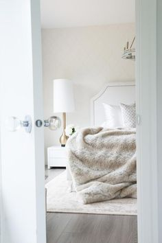 Chic monochromatic bedroom features an accent wall clad in cream arabesque wallpaper lined with a ...