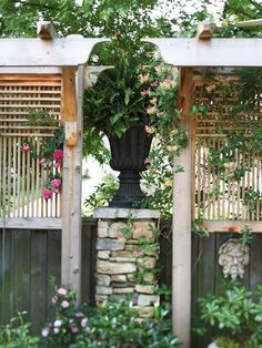An urn set on one of the fence supports looks lovely and provides privacy. Its another way to make a fence seem taller without violating codes