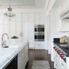 A gray tray ceiling is accented with nickel and glass lanterns illuminating a white center island adorned with polished nickel cup pulls topped with white marble fitted with a curved prep sink and gooseneck faucet placed next to a microwave.
