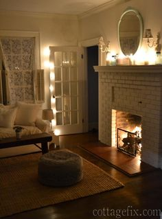 Cottage Fix blog - living room with white candles, twinkle lights, and a cozy…