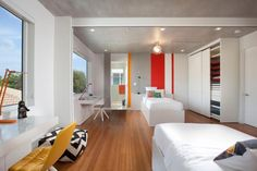 Bedroom: Contemporary Minimalist Bedroom With Energetic Red Wall Accent. minimalist bedroom. twin bed. spherical glass pendant light. white closet. chevron ottoman. yellow tufted chair. wood flooring. vibrant red wall accent.
