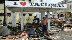 Trail of devastation | People stand under a shelter in Tacloban. Photo: Ted Aljibe/AFP/Getty Images / CNN.com