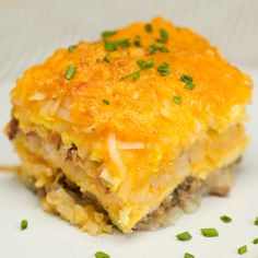 Recipe with video instructions: How to make breakfast hash brown lasagna.  Ingredients: 2 cups breakfast sausage, cooked, 3 cups scrambled eggs, 15 strips bacon, cooked, Butter, 1 lb frozen hash browns, Shredded cheddar cheese, Chives, to garnish