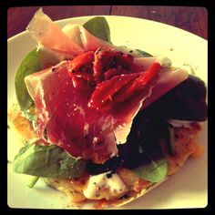 Corn fritters with chive creme fraîche, spinach, and prosciutto topped with sun dried tomatoes