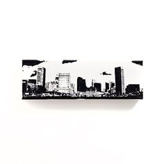 Baltimore Skyline Canvas Wall Art (White with Black, 12 x 4 inches). Baltimore Skyline Canvas Wall Art Can be easily hung on the wall or stood alone on a surface! White Paint with Black Ink. (1) 12 x 4 inch archival & acid-free stretched cotton canvas. © Ink the Print All prints dated and signed on back. *All artwork is painted & printed by hand, resulting in possible minor differences from the photos. This makes each piece unique.