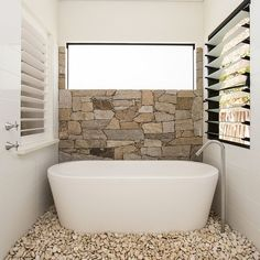 Half wall in natural stone and pebbles on the floor turn the the small bathroom into a relaxing hub [Design: Sam Davison Interiors]